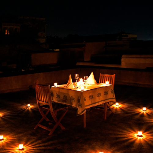 image of dining table outside lit by candle light