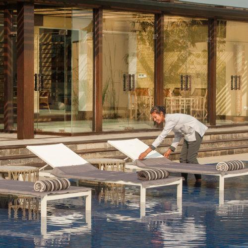 meghauli-serai-maid-making-up-deck-chairs-in-swimming-pool