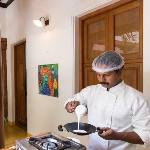 Indian man making pancakes